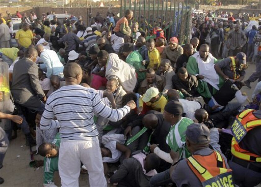 Fans fall on each other prior to the warmup match between North Korea and Nigeria in Johannesburg, South Africa, Sunday June 6, 2010. Thousands of fans stampeded outside the stadium gates of a World Cup warmup game Sunday, five days before the start of soccer's showcase event. Several fans could be seen falling under the crush of people, many wearing Nigeria jerseys. Nigeria was playing North Korea at 10,000-seat Makhulong Stadium in suburban Johannesburg. (AP Photo/Frank Augstein)