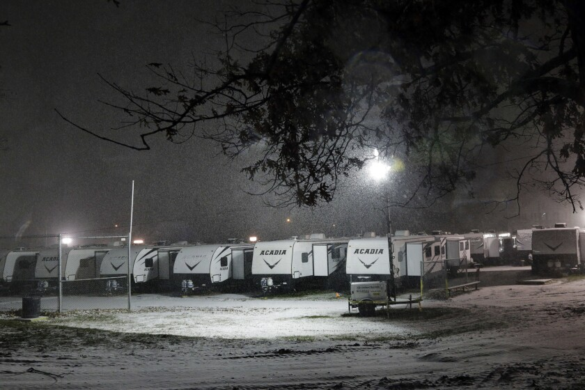 Snow falls on trailers during a storm, Thursday night, Nov. 15, 2018, in Lawrence, Mass. Trailers have been set up to shelter people displaced from their homes due to gas explosions in the Merrimack Valley two months ago.