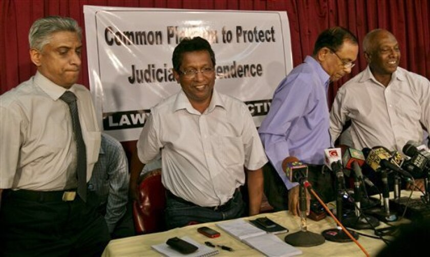 Members of the Lawyers Collective, from left, K.S. Ratnavale, Chrishantha Weliammuna and Jayampathi Wickramaratna leave after a press briefing in Colombo, Sri Lanka, Monday, Jan. 14, 2013. Sri Lanka's president has formally dismissed the country's Chief Justice Shirani Bandaranayake from office after Parliament impeached her in a process that has been widely criticized as an unfair, illegal attempt to ensure a servile judiciary. (AP Photo/Gemunu Amarasinghe)