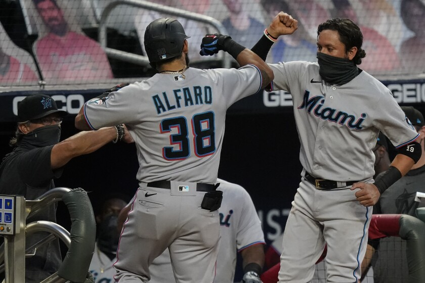 Miami Marlins' Jorge Alfaro, left, celebrates with Miguel Rojas, right, after Alfaro hits a home run during the third inning of the team's baseball game against the Atlanta Braves on Tuesday, Sept. 8, 2020, in Atlanta. (AP Photo/Brynn Anderson)