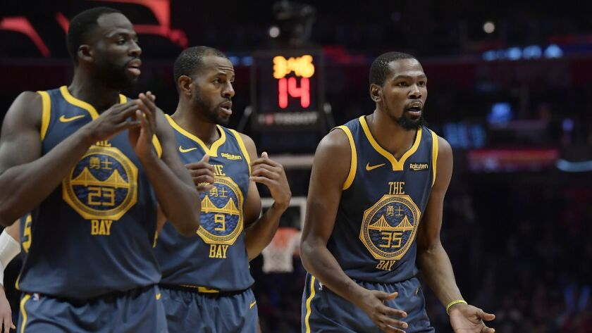 Golden State Warriors forward Kevin Durant, right, reacts as he fouls out of the game while forward Draymond Green, left, and Andre Iguodala look on during the overtime portion against the Clippers.