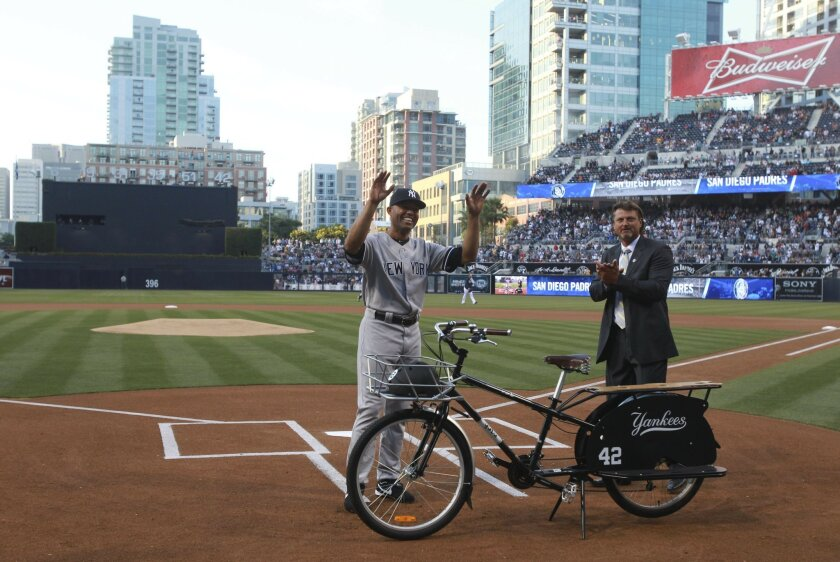 Former Padres closing pitcher Trevor Hoffman, right, presents Yankees' closing pitcher Mariano Rivera with a bicycle during a short ceremony honoring Rivera before the start of the Padres game against the Yankees at Petco Park in San Diego on Friday