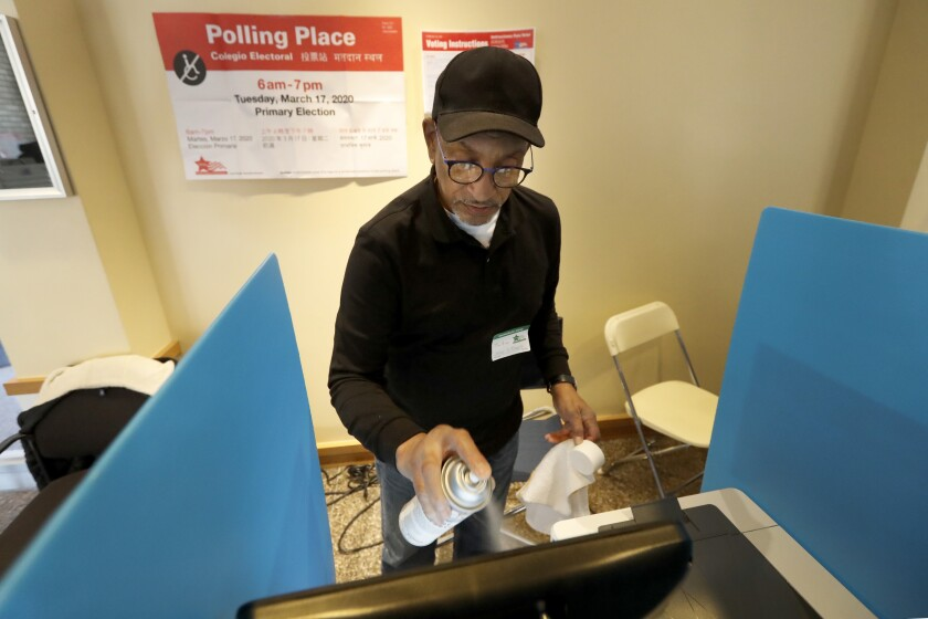 John Davis, a polling judge volunteer, sanitizes a voting machine screen amid concerns about the coronavirus at a polling place in Chicago on Tuesday.