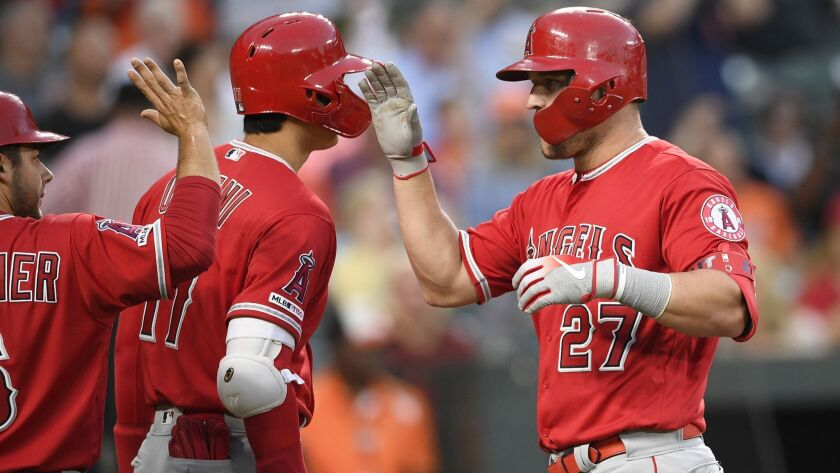 Angels' Mike Trout (27) celebrates his two-run home run with Shohei Ohtani, center, and David Fletcher during the third inning against the Baltimore Orioles on Friday in Baltimore.