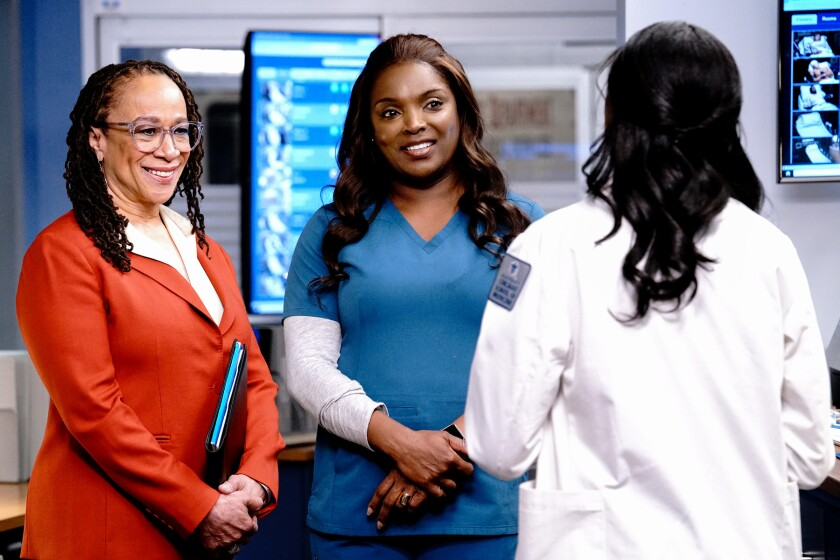 Two women, one in a business suit and another in scrubs, talk to another woman in a white coat with her back turned.