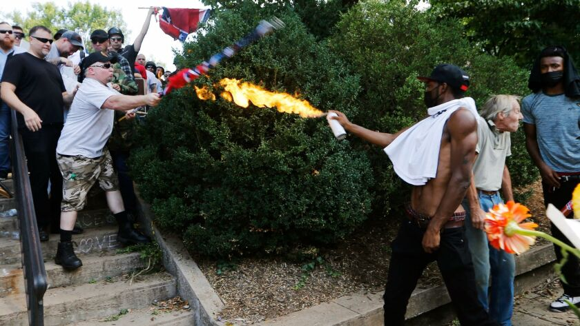 A counterprotester, later identified as Corey Long of Culpeper, Va., uses a lighted spray can against a white nationalist demonstrator at the entrance to Lee Park in Charlottesville in a photo that went viral.
