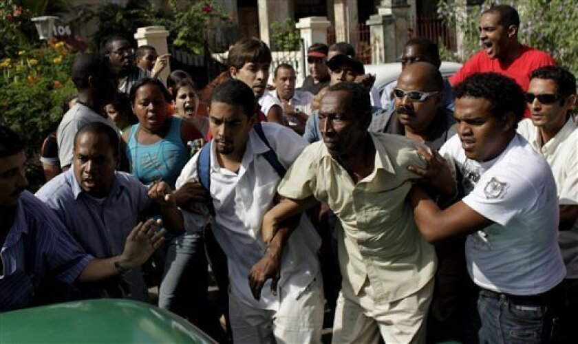 A demonstrator, second from right, is grabbed by unidentified men during a march organized by dissidents to commemorate the Human Rights Day in Havana, Thursday, Dec. 10, 2009. (AP Photo/Javier Galeano)