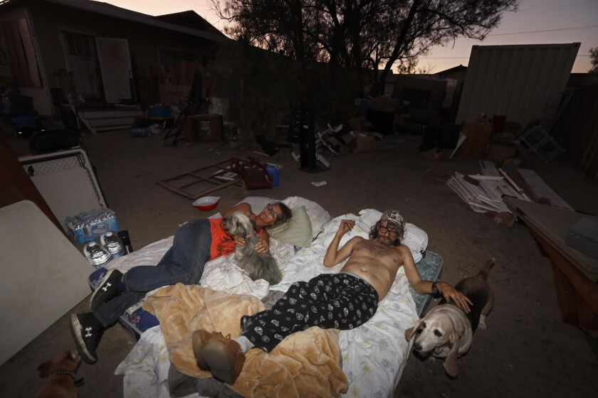 TRONA, CA - JULY 10, 2019 - Ronnie Tolbert, 60, her husband Dan, 62, and their dogs sleep on a pair