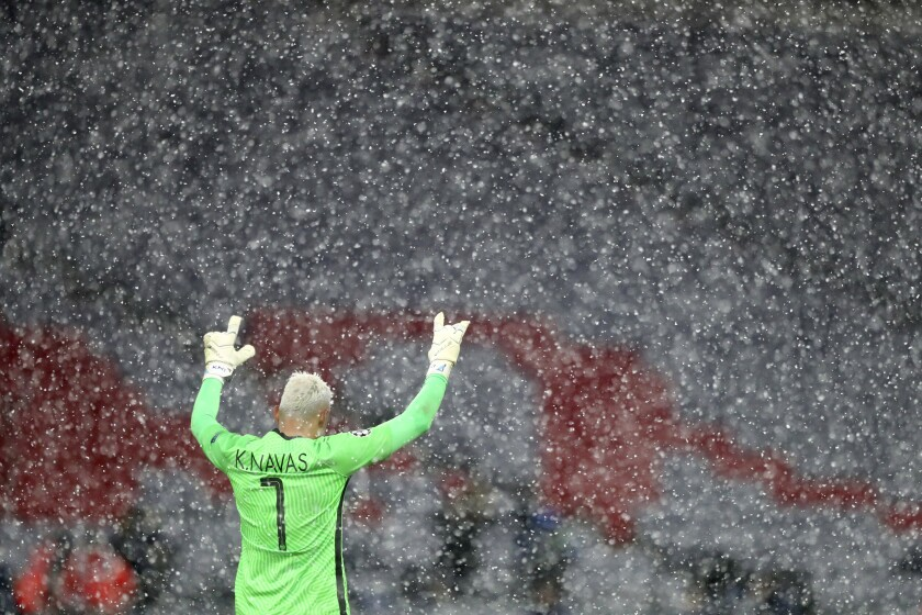 Snow falls as PSG's goalkeeper Keylor Navas reacts after the Champions League quarterfinal soccer match between Bayern Munich and Paris Saint Germain in Munich, Germany, Wednesday, April 7, 2021. PSG won 3-2. (AP Photo/Matthias Schrader)