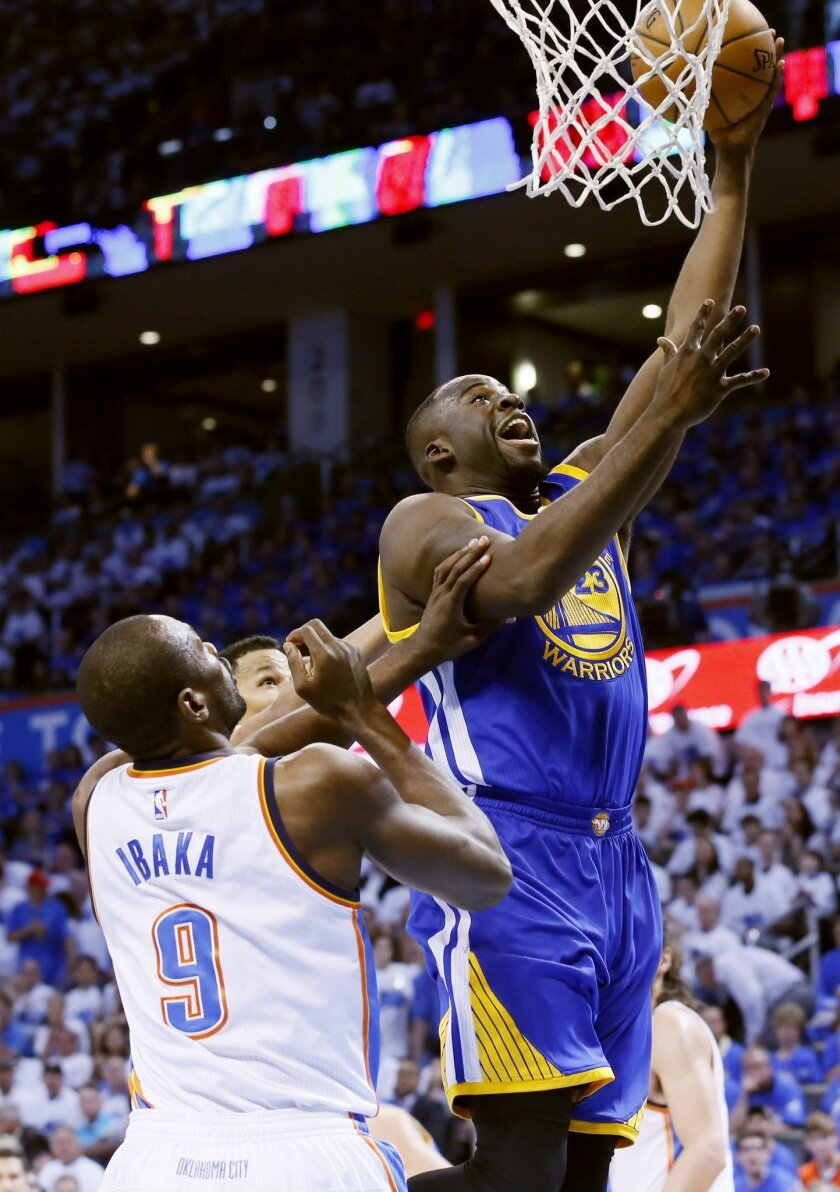 Golden State Warriors forward Draymond Green (23) shoots as Oklahoma City Thunder forward Serge Ibaka (9) defends during the first quarter in Game 3 of the NBA basketball Western Conference finals  in Oklahoma City, Sunday, May 22, 2016. (AP Photo/Sue Ogrocki)
