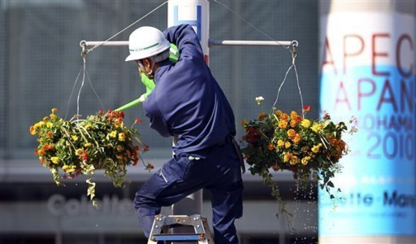 A worker feeds water to flower decoration near the APEC forum venue in Yokohama, near Tokyo, Tuesday, Nov. 9, 2010. Security measures are tighten ahead of the Pacific Rim leaders' meetings. (AP Photo/Junji Kurokawa)