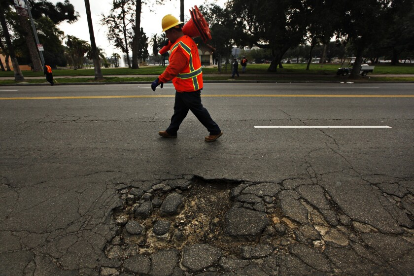 A Bureau of Street Services worker places cones on the road near a large pothole on Mission Road in Los Angeles.