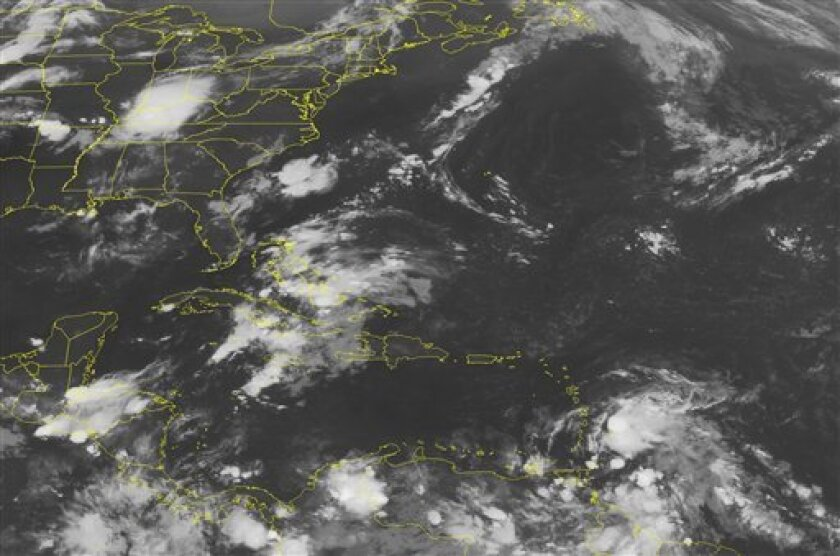 This NOAA satellite image taken Friday, Aug. 03, 2012, at 1:45 a.m. EDT shows Tropical Storm Ernesto just 90 miles east of St. Lucia. This system continues moving west at 22 mph at tropical storm strength with winds up to 50 mph. Tropical storm warnings remain in effect for Barbados, St. Vincent, The Grenadines, Dominica, St. Lucia, Martinique, and Guadeloupe. Expect heavy rains and strong winds in these areas. To the north, a strong tropical wave brings widespread showers and thunderstorms to the Bahamas and Cuba, which moves westward into southern Florida. This system kicks up scattered showers and thunderstorms as it slowly moves westward. (AP Photo/Weather Underground)