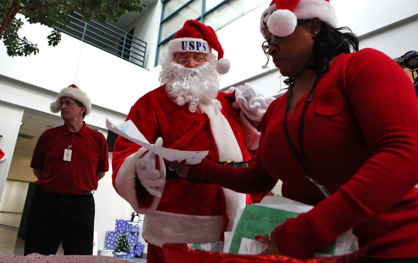 """Postal worker Sandra Smith, right, helps Santa Claus sort through mail sent from children during """"Operation Santa,"""" where the public can adopt and answer letters written to Santa Claus at Los Angeles District Office."""