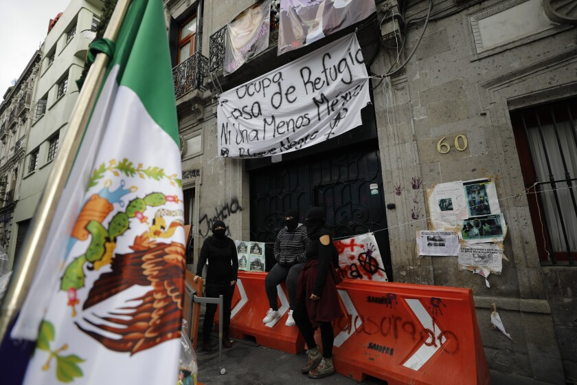 Masked demonstrators sit outside the National Human Rights Commission office in Mexico City.