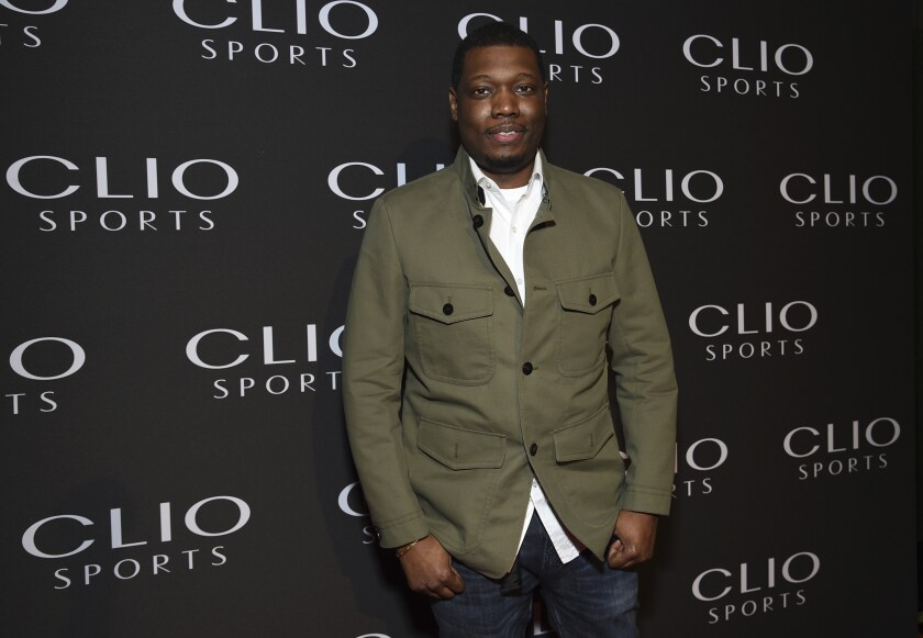 A man posing in a green jacket, white shirt and jeans against a black backdrop