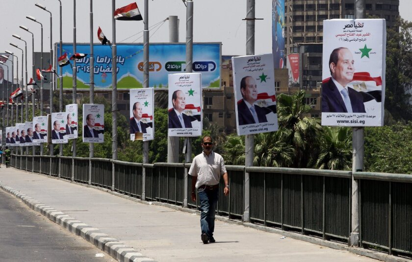 An Egyptian passes under electoral billboards featuring presidential candidate Abdel Fattah Sisi in Cairo on Sunday.