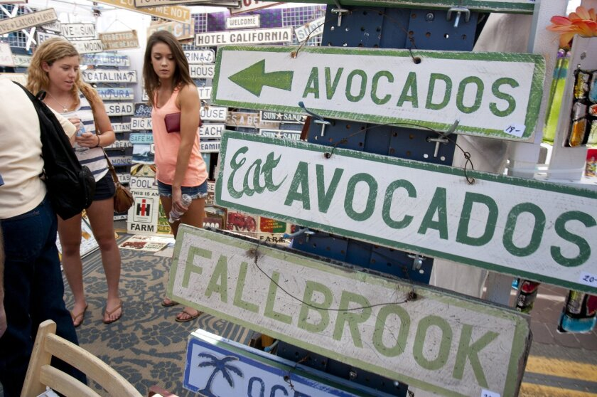A booth with signs for sale features some avocado-style signs at Fallbrook's Annual Avocado Festival in downtown Fallbrook.
