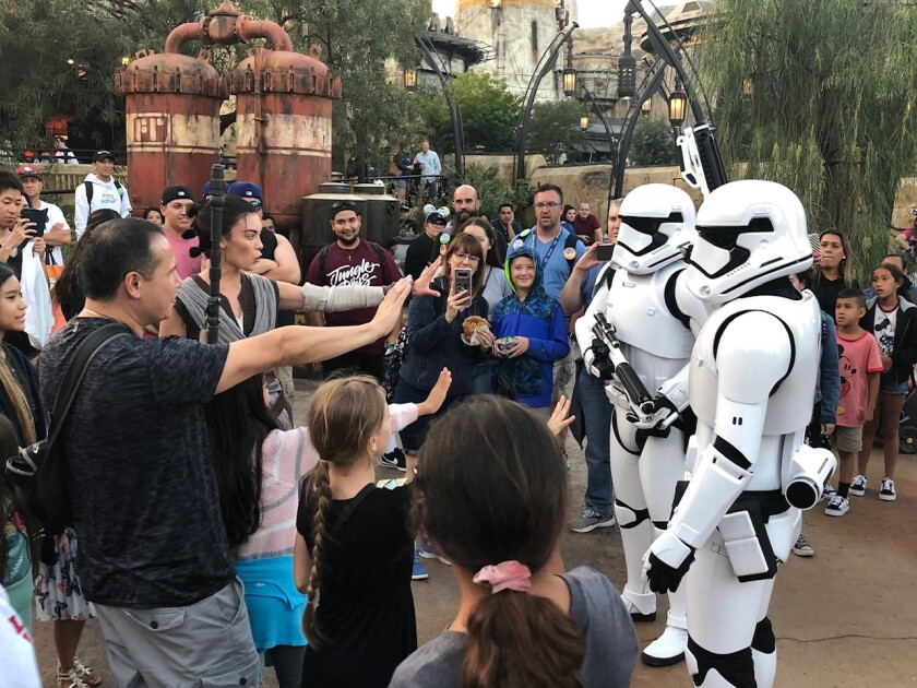 Rey leads a pack of guests to repel Stormtroopers in Star Wars: Galaxy's Edge.