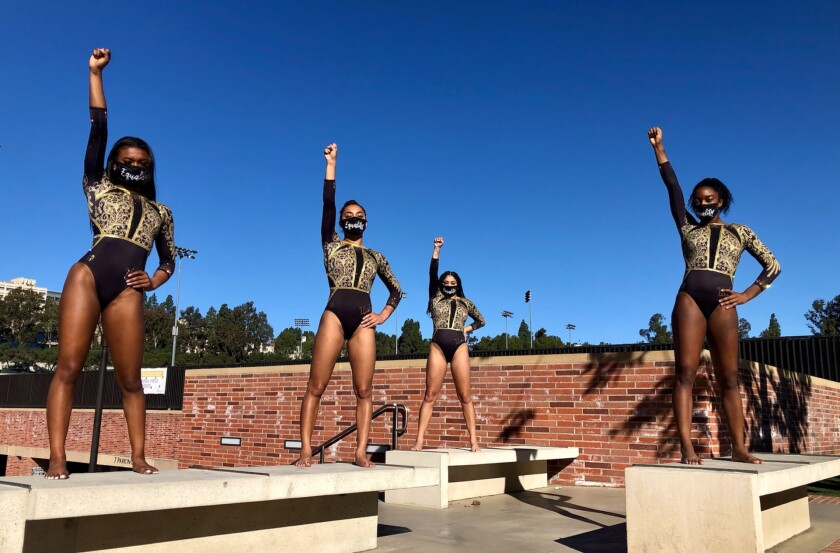 UCLA gymnasts wearing black-and-gold leotards stand on benches with fists raised