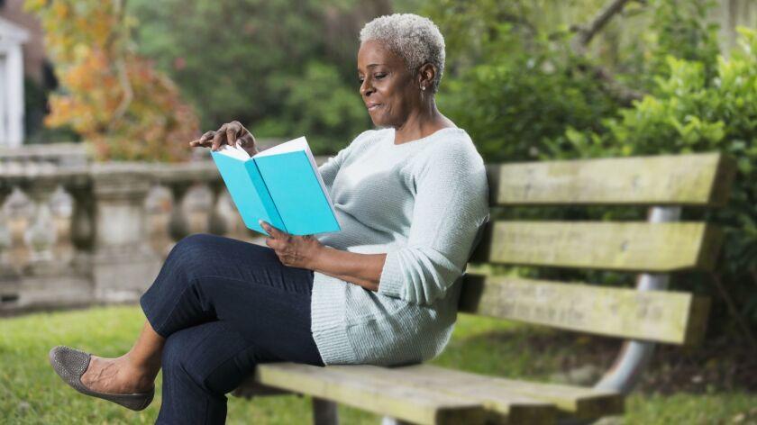 Senior black woman reading a book