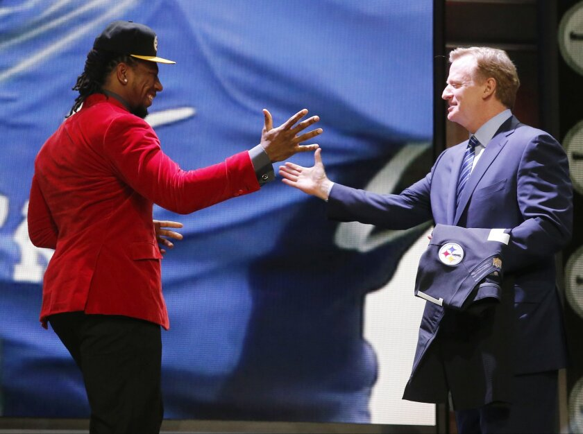 Kentucky linebacker Bud Dupree celebrates with NFL commissioner Roger Goodell after being selected by the Pittsburgh Steelers as the 22nd pick in the first round of the 2015 NFL Draft,  Thursday, April 30, 2015, in Chicago. (AP Photo/Charles Rex Arbogast)