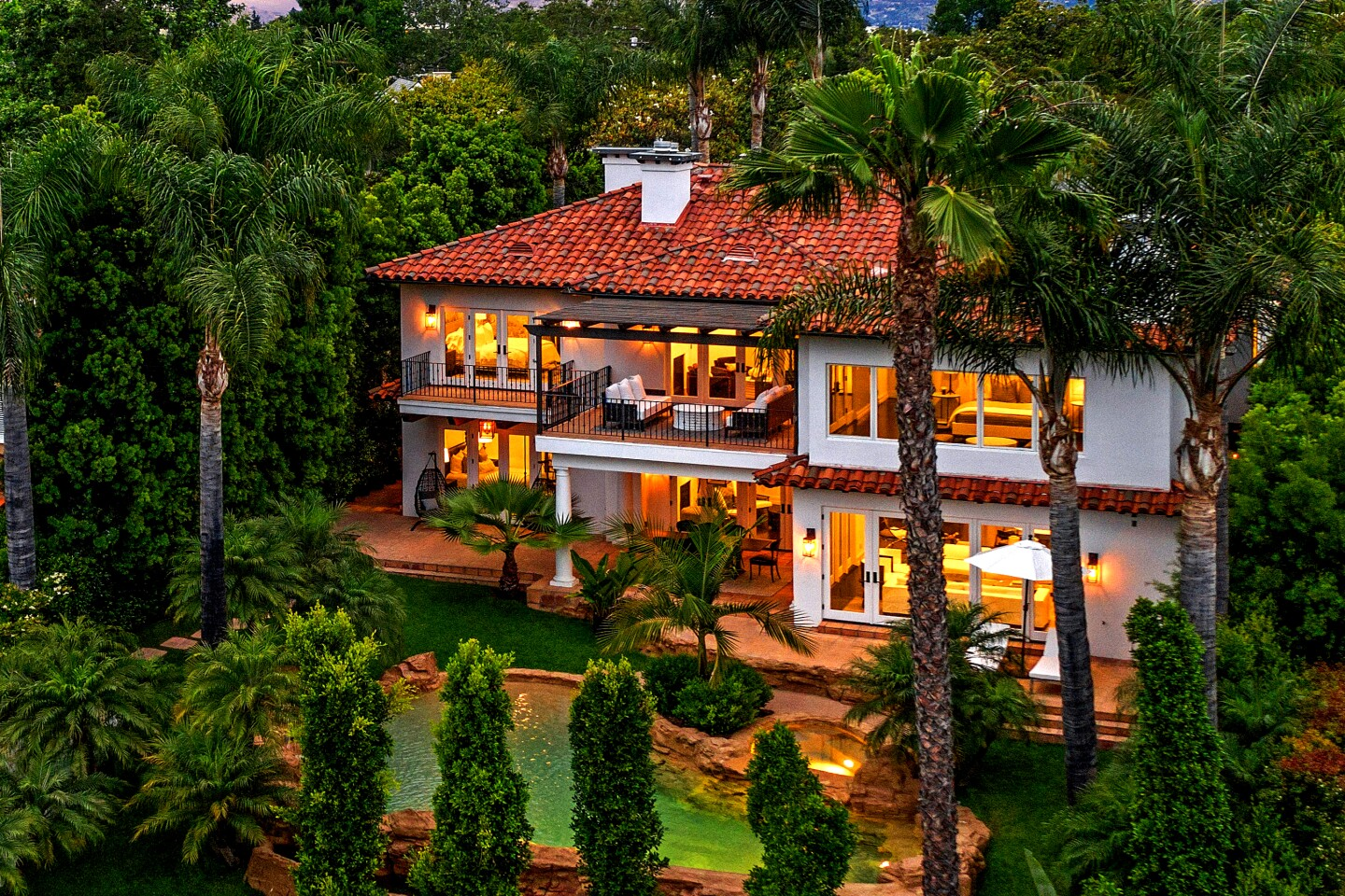 The two-story home, listed for a dollar shy of $8 million, sits on more than a third of an acre overlooking the lake. Polished to a fine sheen, the designer-done interiors feature dark wood floors that stand out against white walls and cabinetry. Outside, a lagoon-style swimming pool with a baja deck extends outward below the lake. Below the pool is a small dock for paddleboats. A two-room recording studio lies beneath the home where there's also a subterranean garage.