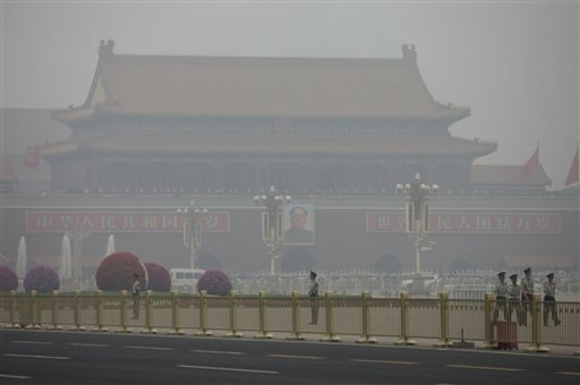 In this Sunday June 2, 2013 photo, paramilitary policemen patrol on Tiananmen Square on a polluted day in Beijing, China. China's Cabinet has announced Friday, June 15, 2013 measures to curb the country's notorious air pollution, one of the many environmental challenges facing the country that are