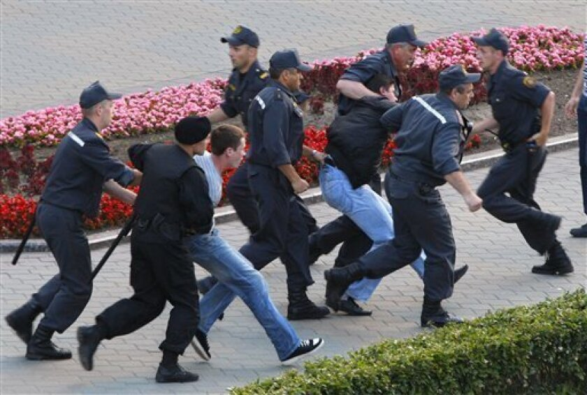 """Belarusian policemen detain protesters during an action """"Revolution via social network"""" in Minsk, Belarus, Wednesday, June 22, 2011. Human rights advocates and activists in Belarus are claiming that security agents have interrogated social media activists who called for an opposition rally across the authoritarian ex-Soviet nation. (AP Photo/Sergei Grits)"""