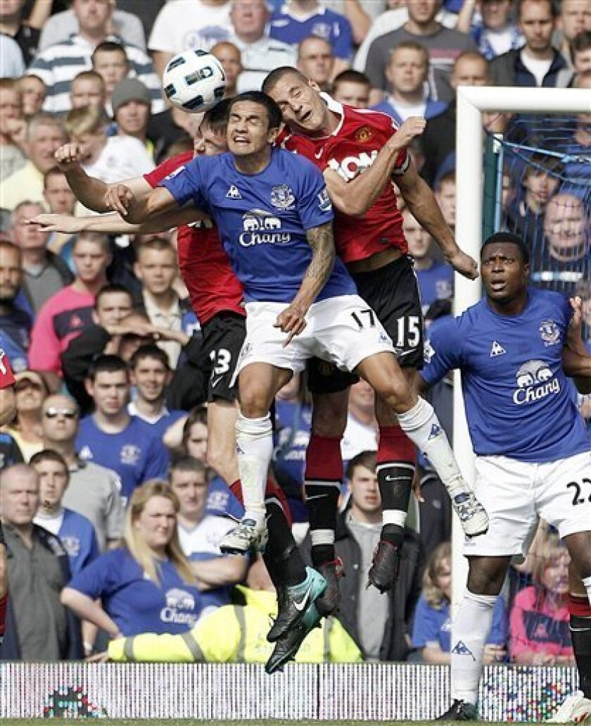 Everton's Tim Cahill, centre, challenges for the ball with Manchester United's Jonathan Evans, left, and Nemanja Vidic during the English Premier League soccer match at Goodison Park, Liverpool, England, Saturday Sept. 11, 2010. The match ended in a 3-3 draw. (AP Photo/Peter Byrne, PA)