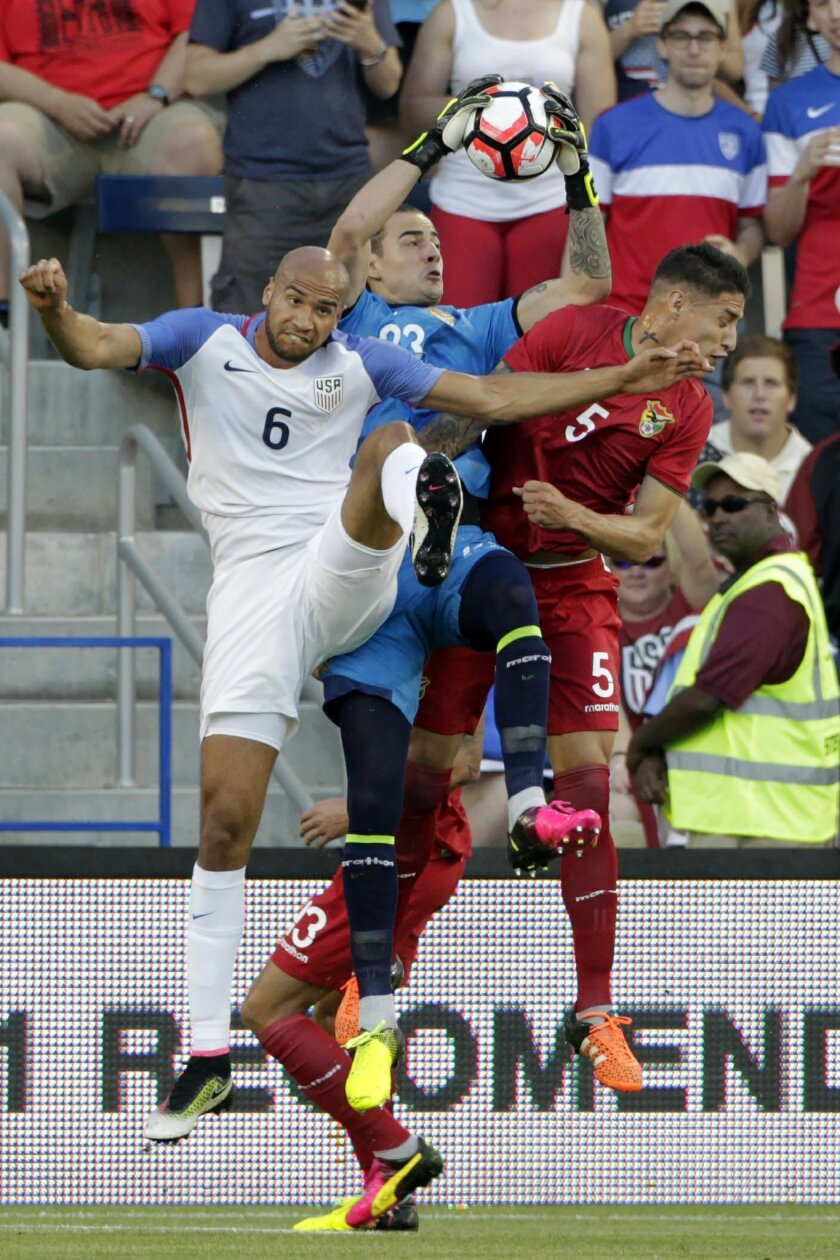 Bolivia goalkeeper Guillermo Viscarra (23) grabs a corner kick as U.S. defender John Brooks (6) pressures and Bolivia's Nelson Cabrera (5) defends during the first half of an international friendly soccer match, Saturday, May. 28, 2016, in Kansas City, Kan. (AP Photo/Colin E. Braley)
