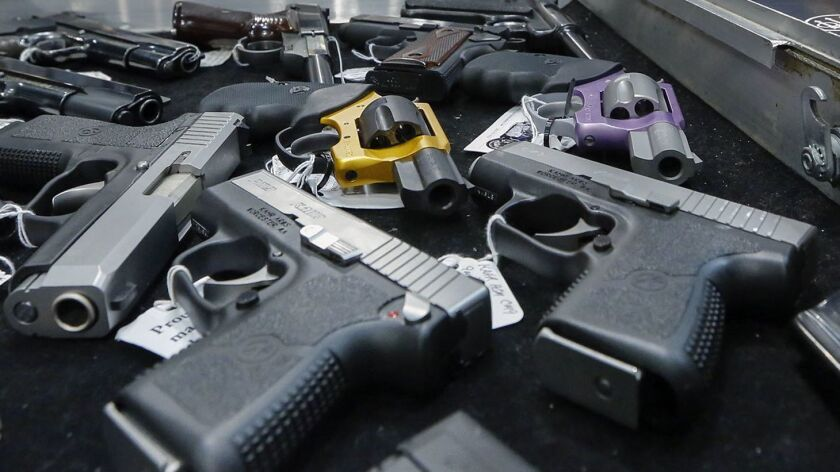 FILE - In this Jan. 26, 2013, file photo, handguns are displayed on a vendor's table at an annual gu