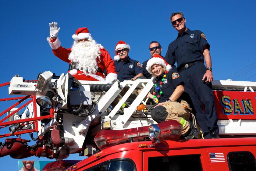 Santa Claus arrives PB-style, atop a fire truck, accompanied by first-responders from Station 21.