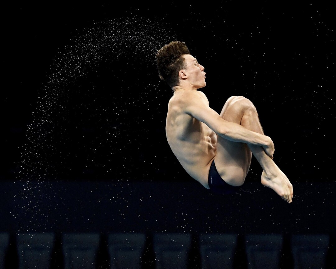 A diver holds his legs in midair.