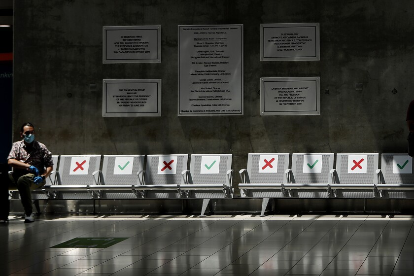 A man wearing mask sits on an airport bench a seat apart in line with social distancing rules at Cyprus' main airport in Larnaca, on Tuesday, June 9, 2020. Cyprus re-opened its airports on Tuesday to a limited number of countries after nearly three months of commercial air traffic as a result of a strict lockdown aimed at staving off the spread of COVID-19. (AP Photo/Petros Karadjias)