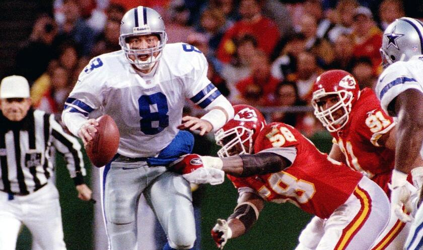Cowboys quarterback Troy Aikman is sacked by Chiefs linebacker Derrick Thomas during a game in 1998.