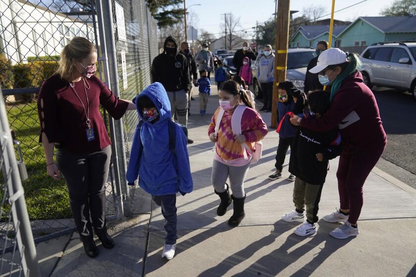 Assistant Principal Janette Van Gelderen, left, welcomes students at Newhall Elementary in Santa Clarita, Calif.