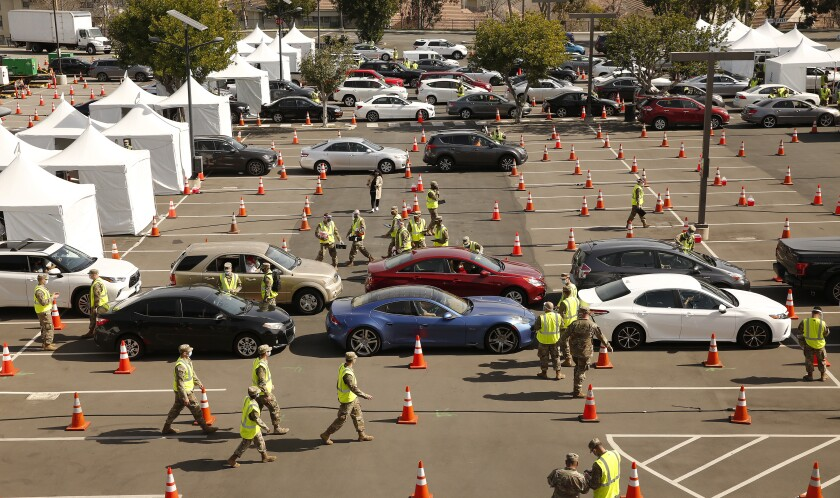 Cars line up between orange cones in a Cal State Los Angeles  parking lot