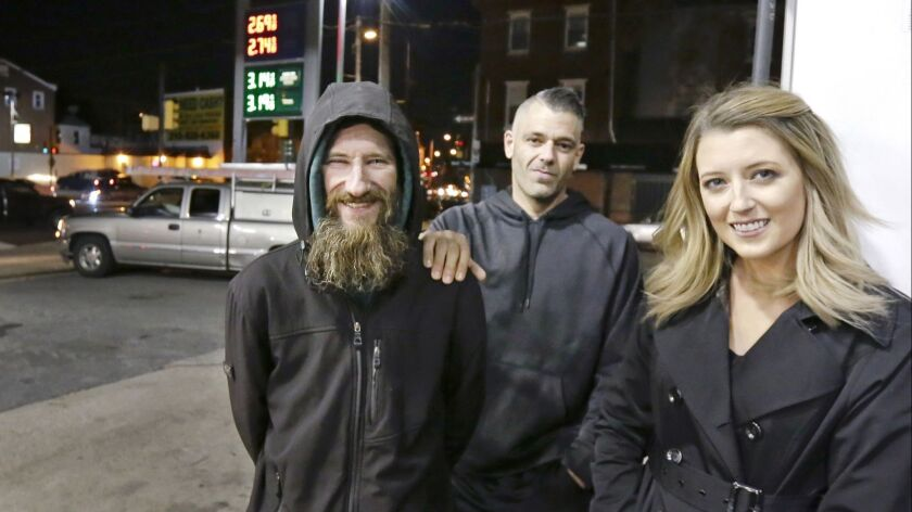 FILE – In this Nov. 17, 2017, file photo, Johnny Bobbitt Jr., left, Kate McClure, right, and McClu