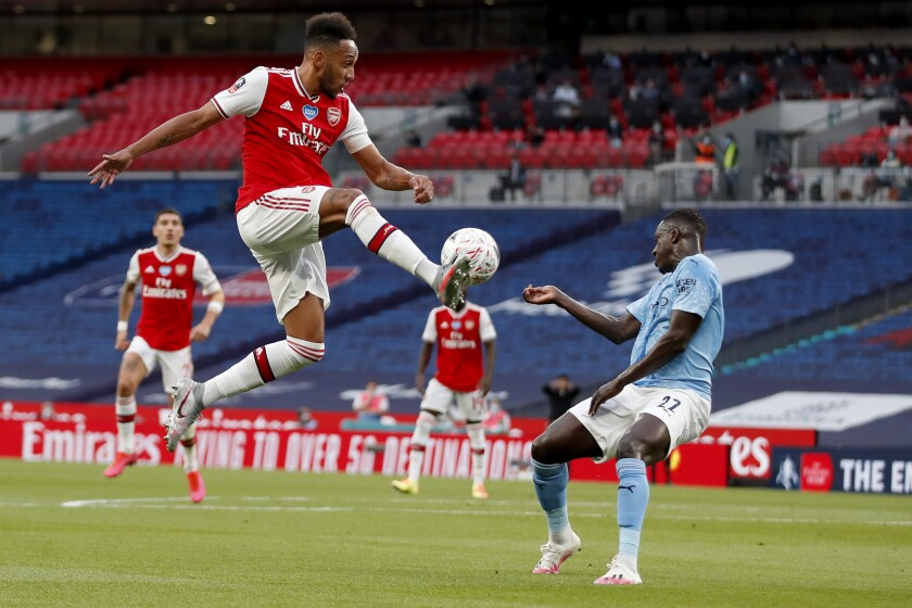 Arsenal's Pierre-Emerick Aubameyang, left, is airborne as he kicks at the ball away from Manchester City's Benjamin Mendy during the FA Cup semifinal soccer match between Arsenal and Manchester City at Wembley in London, England, Saturday, July 18, 2020. (AP Photo/Matt Childs,Pool)
