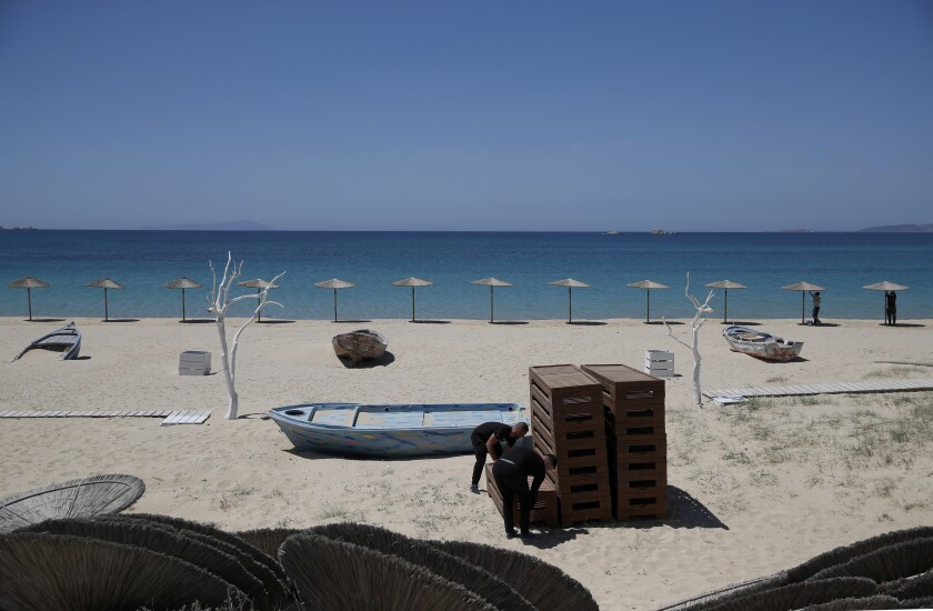 Workers arrange sunbeds as others install umbrellas at Plaka beach on the Aegean island of Naxos, Greece, Wednesday, May 12, 2021. With debts piling up, southern European countries are racing to reopen their tourism services despite delays in rolling out a planned EU-wide travel pass. Greece Friday became the latest country to open up its vacation season as it dismantles lockdown restrictions and focuses its vaccination program on the islands. (AP Photo/Thanassis Stavrakis)