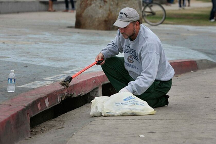 Ocean Beach resident Tom Racanelli fishes out marshmallows and other debris from the opening of a storm drain on Monday, July 5, 2010, the morning after the traditional -- and messy -- marshmallow fight on the beach.