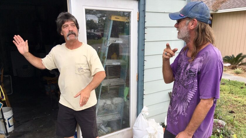 Dwight Williams, left, and Timothy Thomas discuss whether to evacuate their neighborhood in Panama C