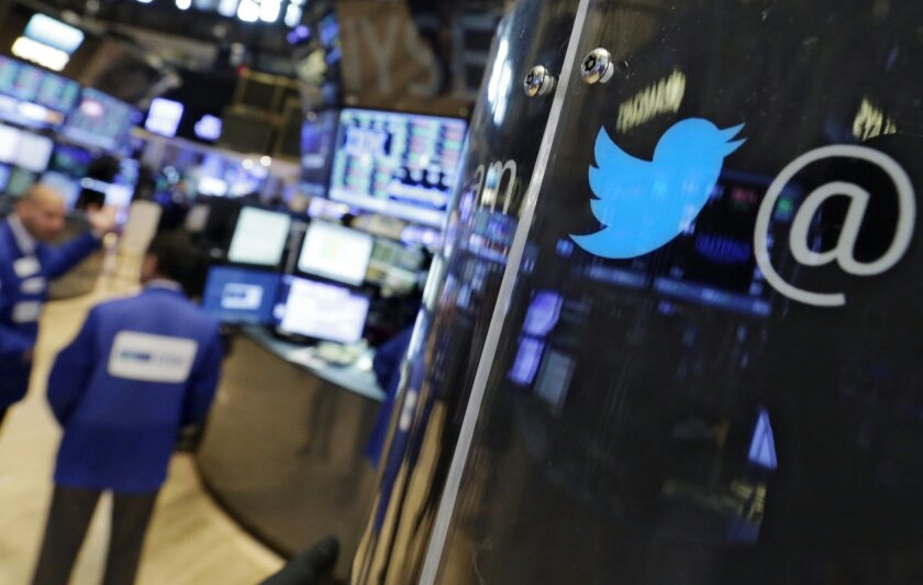 FILE - In this July 28, 2015, file photo, the logo for Twitter adorns a phone post on the floor of the New York Stock Exchange. Twitter is tweaking its timeline. The social media site will let people turn on a setting that lets popular tweets related to people you follow show up first in your timel