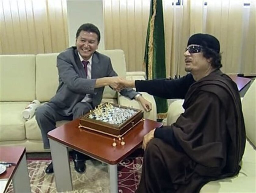 FILE - In this file image taken from video on Sunday, June 12, 2011 provided by FIDE President Kirsan Ilyumzhinov's press service, Libyan leader Moammar Gadhafi, right, shakes hands with visiting president of the World Chess Federation Kirsan Ilyumzhinov, before a game of chess, in Tripoli. The Rus