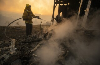 LOS ANGELES, CALIF. -- MONDAY, OCTOBER 28, 2019: A LA City firefighter keeps down flames at a burned home in the 1100 block of Tigertail Rd. in the Brentwood Heights neighborhood of Los Angeles, Calif., on Oct. 28, 2019. (Brian van der Brug / Los Angeles Times)