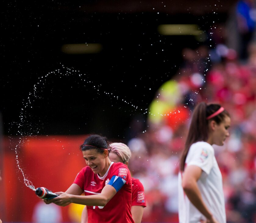 Canada's Christine Sinclair, left, sprays water in celebration as Switzerland's Rahel Kiwic, right, leaves the field after Canada defeated Switzerland 1-0 in the FIFA Women's World Cup round of 16 soccer action in Vancouver, British Columbia, Canada, on Sunday, June 21, 2015 . (Darryl Dyck/The Cana