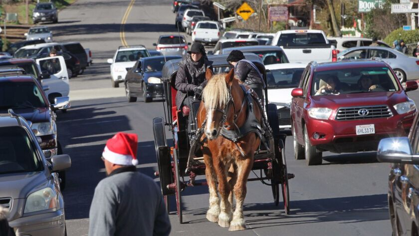 A Belgian draft horse named pulls a carriage full of passengers on busy Main Street in downtown Julian.