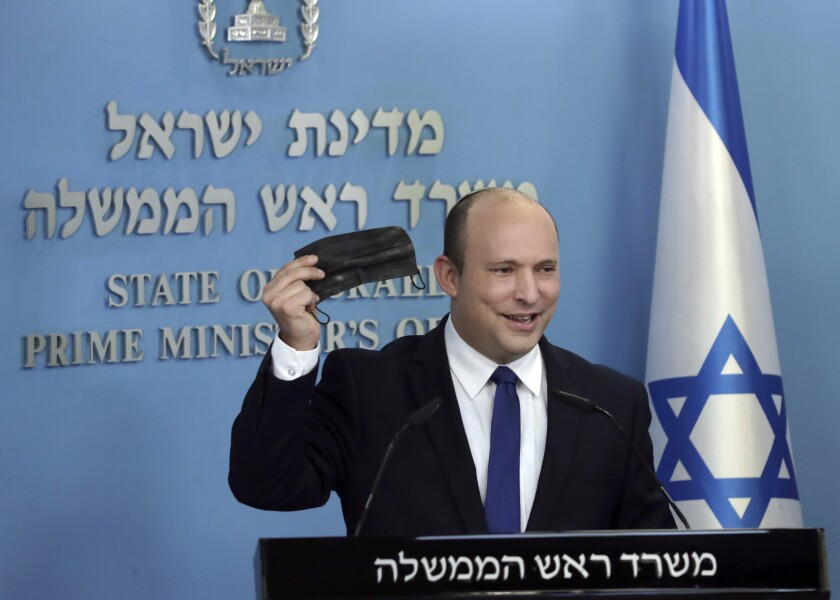 Israeli Prime Minister Naftali Bennett holds up a face mask as he delivers a statement on the coronavirus situation, in Jerusalem Wednesday, July 14, 2021. Bennett said Wednesday that Israel can beat a concerning rise in new coronavirus cases without a nationwide shutdown, but he called on people to wear masks indoors and otherwise comply with safety rules. (AP Photo/Maya Alleruzzo)