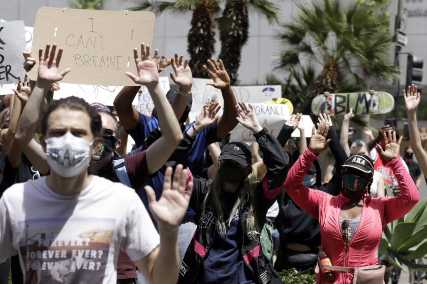 Protesters wear masks during a demonstration on Sunday in downtown Los Angeles. L.A. County remains a hot spot amid the coronavirus outbreak.(Myung J. Chun / Los Angeles Times)